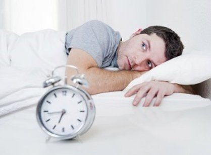 Man with insomnia trying to sleep next to an alarm clock.
